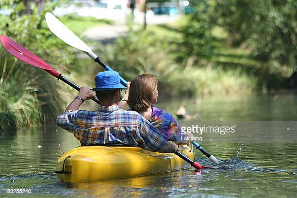 Rear view of couple kayaking with oars in sync