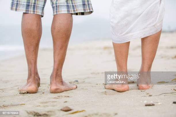 Rear View of Couple Legs Walking on Beach