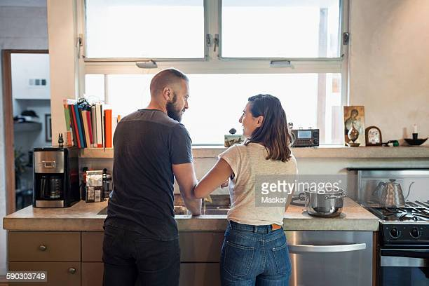 rear view of couple looking at each other in kitchen - chores stock pictures, royalty-free photos & images