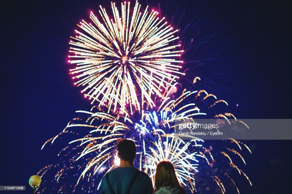 Rear View Of Couple Looking At Firework Display At Night : Stock Photo