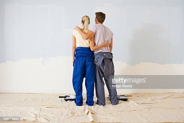 Rear view of couple looking at paint on wall