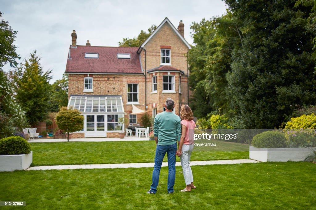 Rückansicht des Paares auf dem Rasen am Haus suchen : Stock-Foto