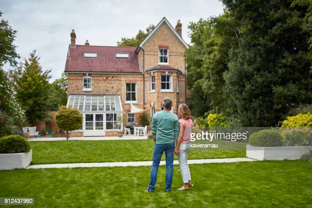 rear view of couple on grass looking at house - outdoors stock pictures, royalty-free photos & images
