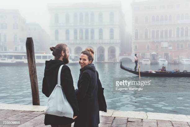 rear view of couple on misty canal waterfront, venice, italy - gondola traditional boat stock pictures, royalty-free photos & images