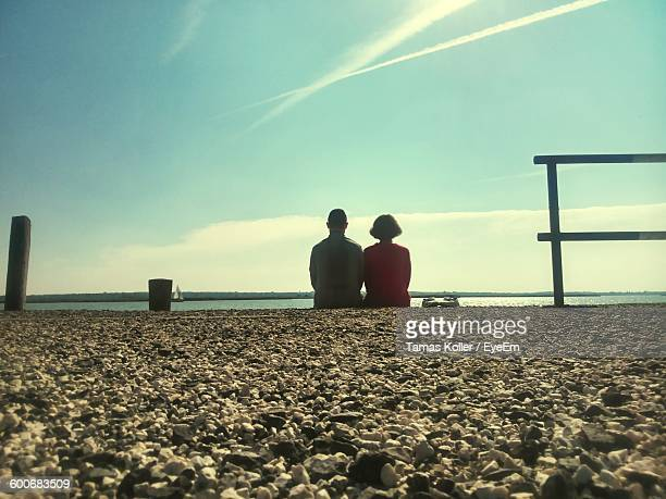 Rear View Of Couple Overlooking Calm Sea