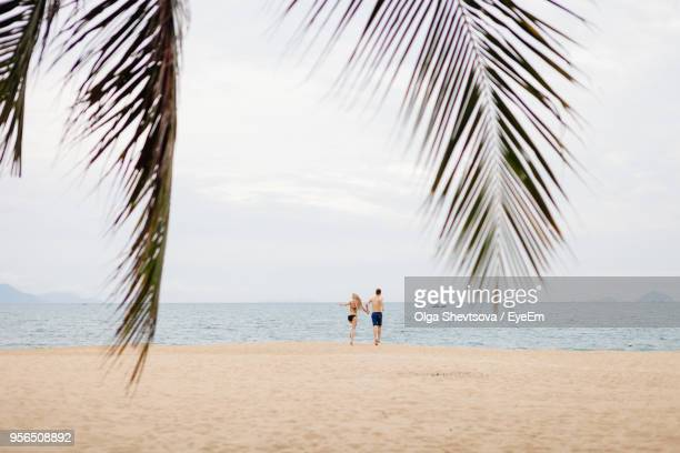 Rear View Of Couple Running On Beach Against Sky