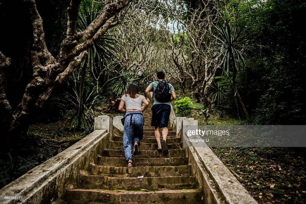 Rear view of couple running up steps to Mount Phousi, Luang Prabang, Laos : Stock Photo