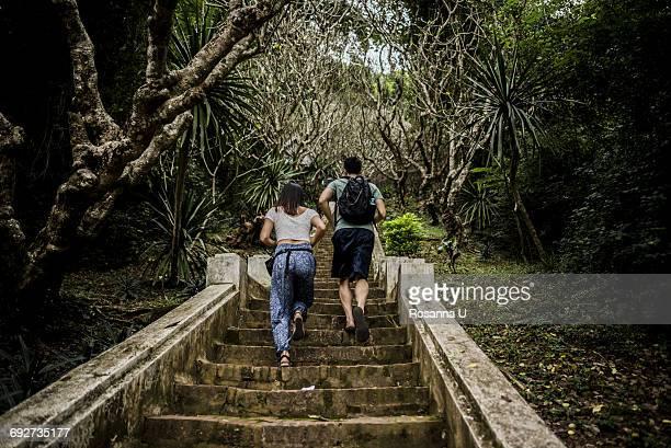 Rear view of couple running up steps to Mount Phousi, Luang Prabang, Laos