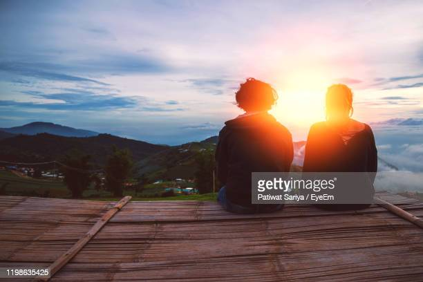 rear view of couple sitting against mountains during sunset - observation point stock pictures, royalty-free photos & images
