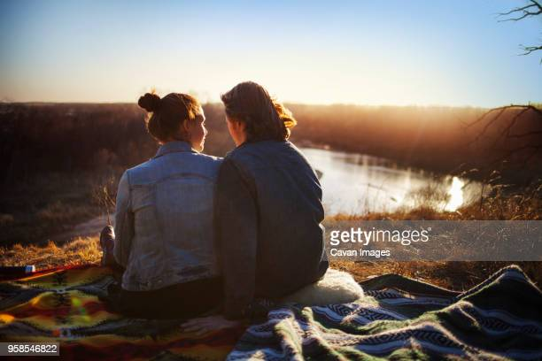 Rear view of couple sitting by lake during sunset