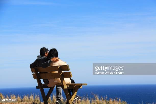 Rear View Of Couple Sitting On Bench Against Sea
