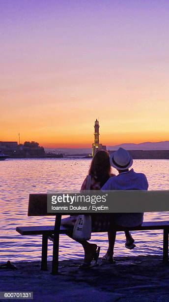 Rear View Of Couple Sitting On Bench At Shore During Sunset