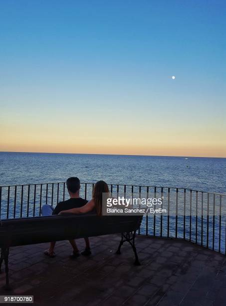 Rear View Of Couple Sitting On Bench By Railing Over Sea Against Sky During Sunset