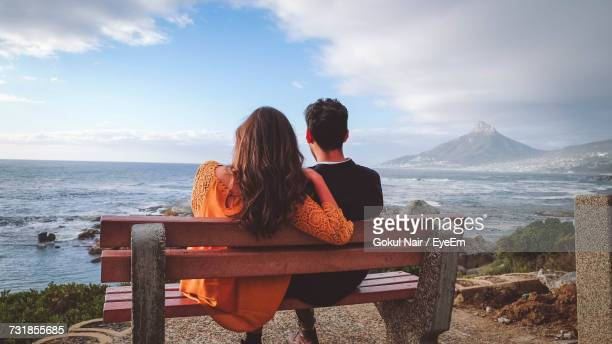 Rear View Of Couple Sitting On Bench While Looking At Sea Against Sky