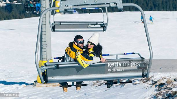 Rear view of couple sitting on chairlift in ski resort