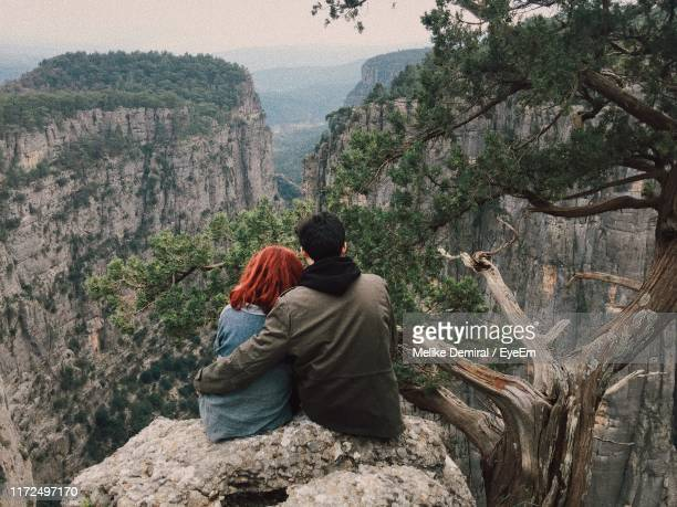 rear view of couple sitting on cliff against mountains - demiral stock pictures, royalty-free photos & images