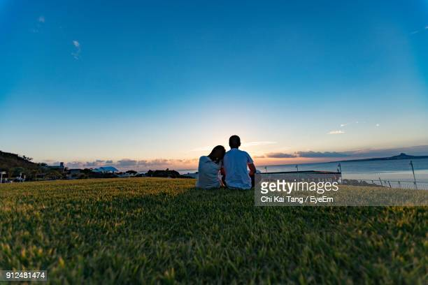 Rear View Of Couple Sitting On Field Against Sky