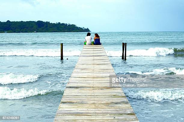 Rear View Of Couple Sitting On Jetty During Sunny Day