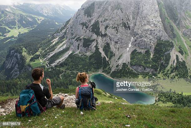 Rear View Of Couple Sitting On Mountain At Ehrwald
