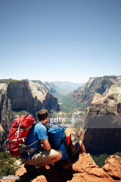 Rear view of couple sitting on mountain cliff against clear sky