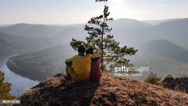 Rear View Of Couple Sitting On Mountain Peak Against Sky