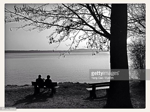 rear view of couple sitting on park bench at lake shore - köpenick stock pictures, royalty-free photos & images