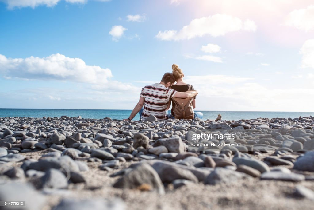Rear View Of Couple Sitting On Pebbles At Beach : Stock Photo