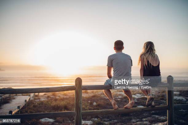 rear view of couple sitting on railing against beach - sitting foto e immagini stock
