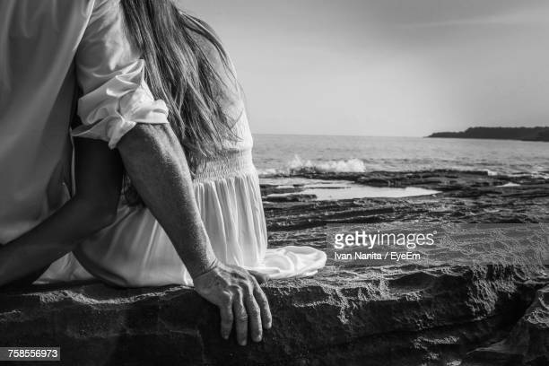Rear View Of Couple Sitting On Rock At Beach Against Sky