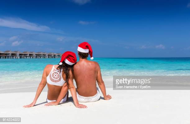rear view of couple sitting on shore at beach against sky - caribbean christmas stock pictures, royalty-free photos & images