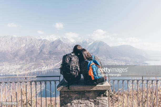 Rear view of couple sitting on terrace wall over mountain lakeside, Monte San Primo, Italy