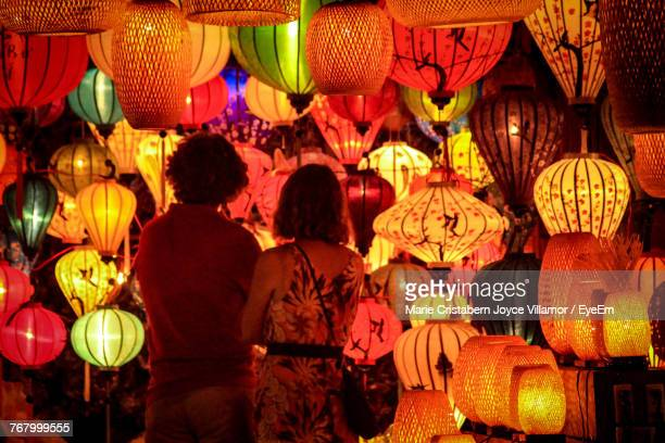 rear view of couple standing against illuminated lanterns hanging at night - lantern festival stock photos and pictures