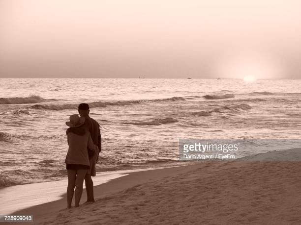 rear view of couple standing at beach against sky - destin beach stock pictures, royalty-free photos & images
