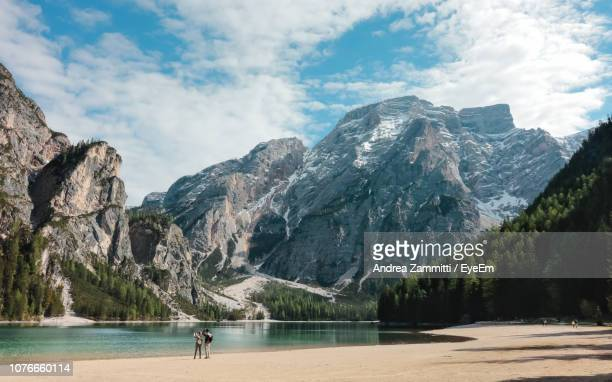 rear view of couple standing by lake and mountains against cloudy sky - pragser wildsee stock pictures, royalty-free photos & images