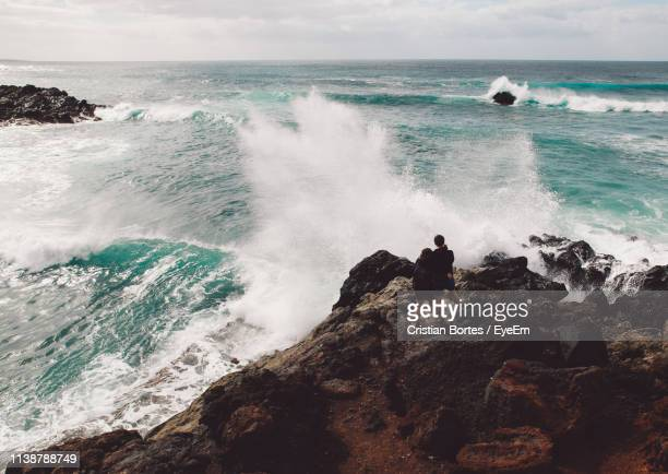 rear view of couple standing on cliff by sea - bortes stock pictures, royalty-free photos & images