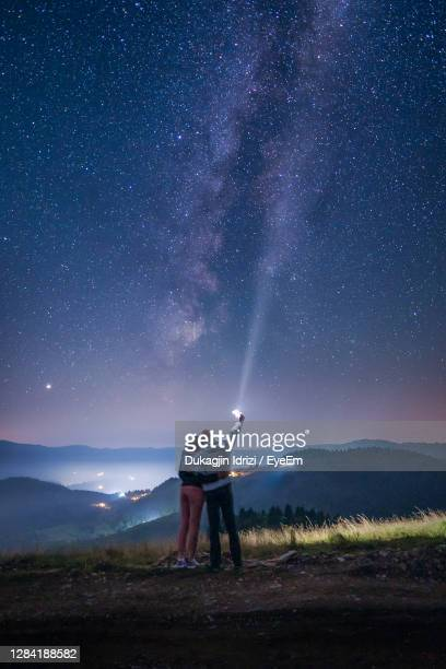 rear view of couple standing on field against sky at night - star field stock pictures, royalty-free photos & images