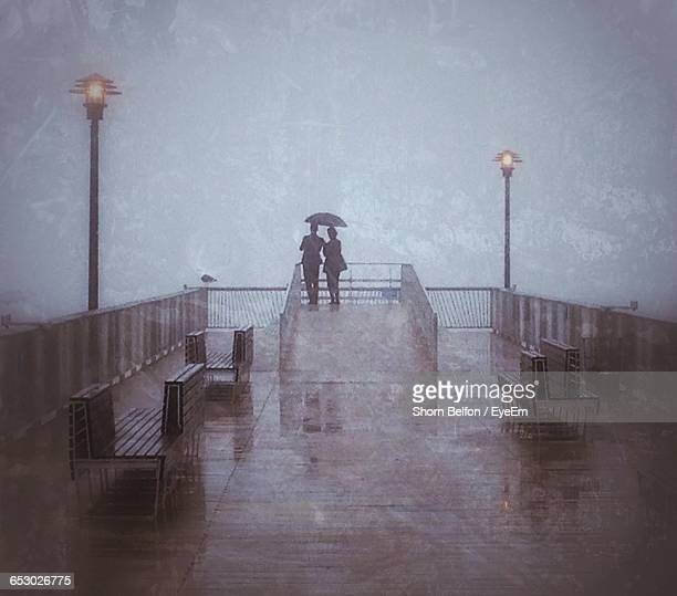 Rear View Of Couple Standing On Observation Point During Rainy Season