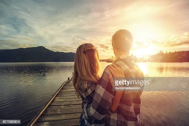 Rear view of couple standing on pier looking at lake