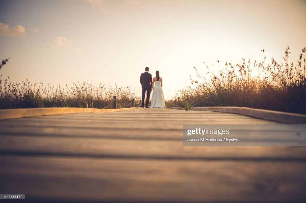 Rear View Of Couple Standing On Road Against Sky : Stock Photo