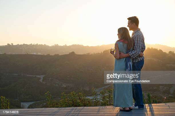 Rear view of couple standing together at sunset