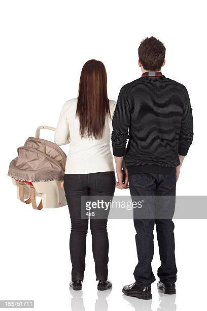 Rear view of couple standing with a baby carrier