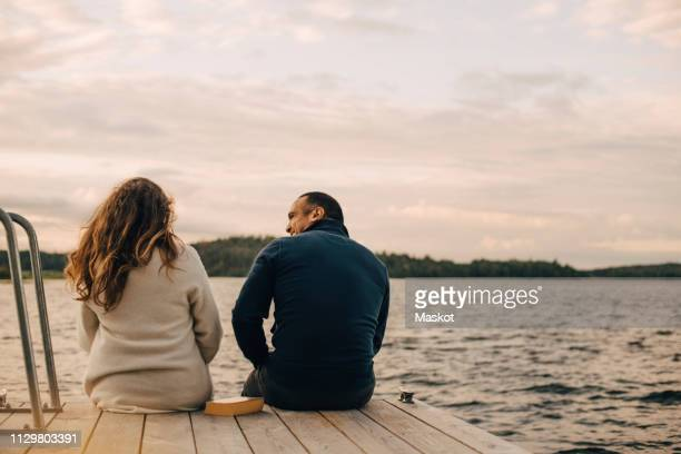 rear view of couple talking while sitting on jetty by lake against sky - jetty stock pictures, royalty-free photos & images