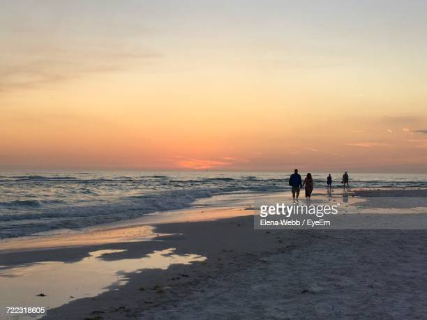 rear view of couple walking at beach against sky during sunset - sarasota stock photos and pictures