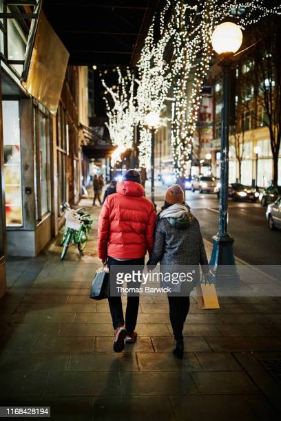 rear view of couple walking down street holding hands while holiday shopping - 防寒着 ストックフォトと画像