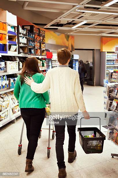 Rear view of couple walking in supermarket