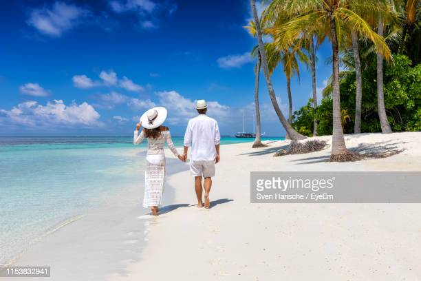 rear view of couple walking on beach against sky - honeymoon stock pictures, royalty-free photos & images