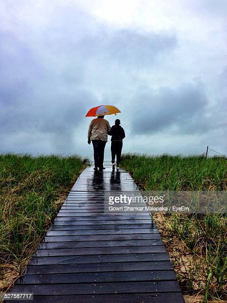 rear view of couple walking on boardwalk - wide shot stock pictures, royalty-free photos & images