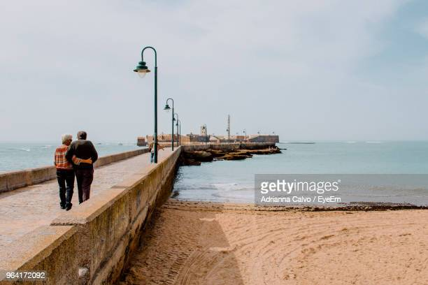 Rear View Of Couple Walking On Pier At Beach Against Sky