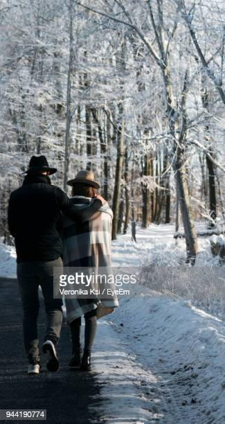 rear view of couple walking on road in winter - ksi stock photos and pictures