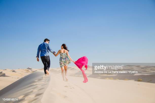 rear view of couple walking on sand at desert against sky - chihuahua desert stock pictures, royalty-free photos & images